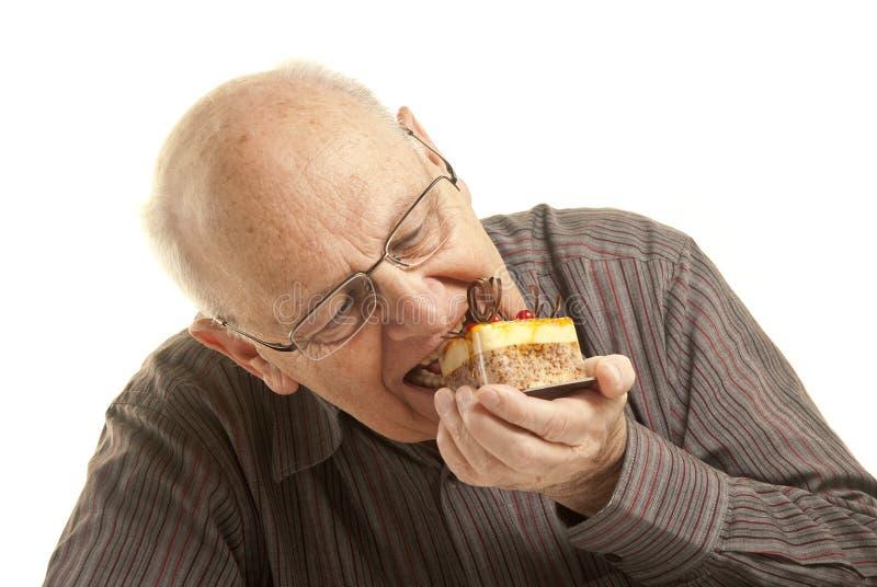 Ανώτερο άτομο που τρώει ένα κέικ στοκ φωτογραφία
