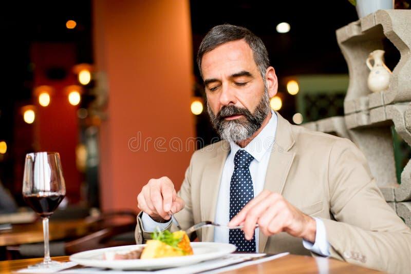 Ανώτερο άτομο που τρώει το μεσημεριανό γεύμα στο εστιατόριο στοκ φωτογραφία