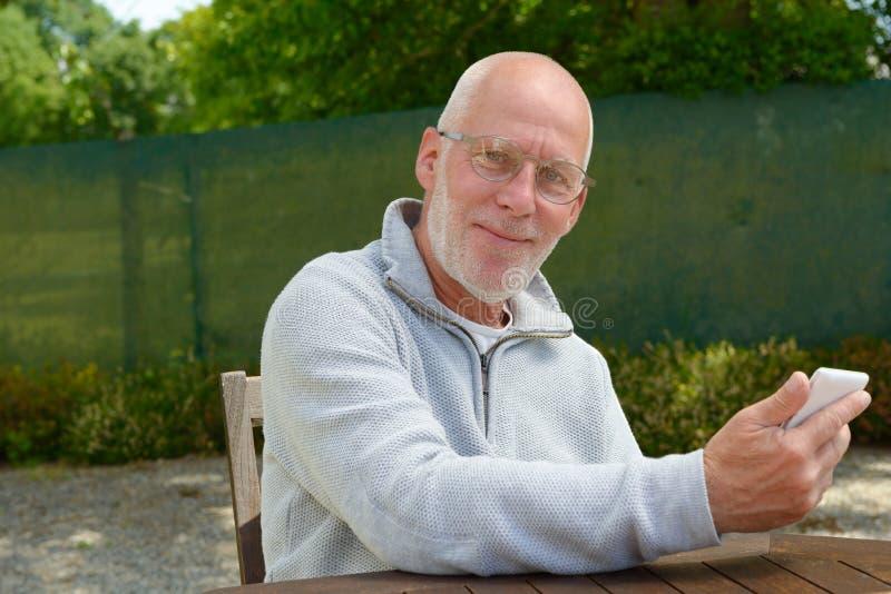 Ανώτερο άτομο που χρησιμοποιεί το κινητό τηλέφωνο έξω στοκ φωτογραφία με δικαίωμα ελεύθερης χρήσης