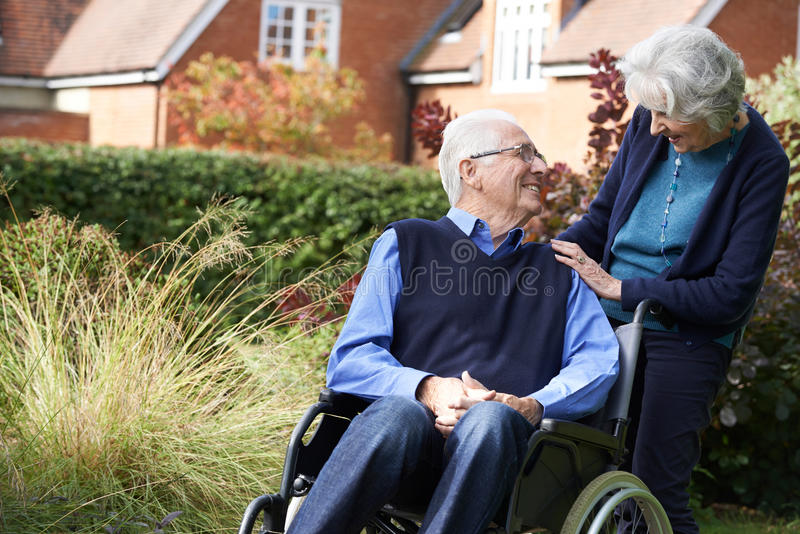 Ανώτερο άτομο που ωθείται στην αναπηρική καρέκλα από τη σύζυγο στοκ φωτογραφία με δικαίωμα ελεύθερης χρήσης