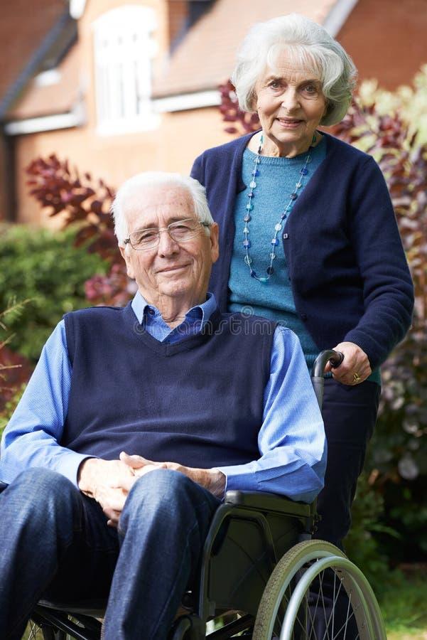 Ανώτερο άτομο στην αναπηρική καρέκλα που ωθείται από τη σύζυγο στοκ εικόνες
