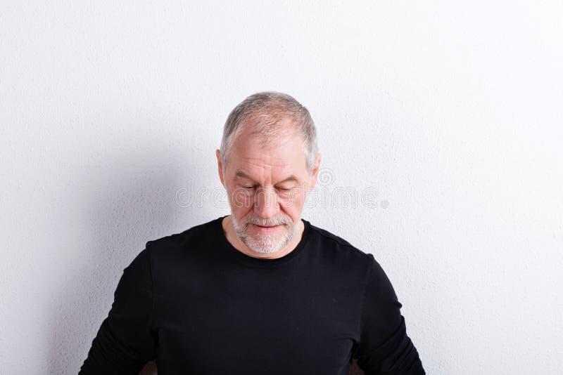 Ανώτερο άτομο στη μαύρη μπλούζα, που κοιτάζει κάτω, πυροβολισμός στούντιο στοκ εικόνες