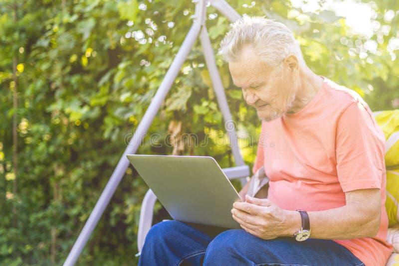 Ανώτερο άτομο eldery που εργάζεται σε μια συνεδρίαση lap-top στο θερινό κήπο στοκ εικόνες