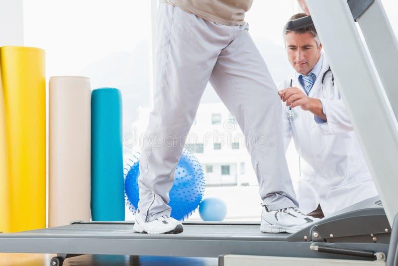 Ανώτερο άτομο treadmill με το σκύψιμο θεραπόντων στοκ εικόνα