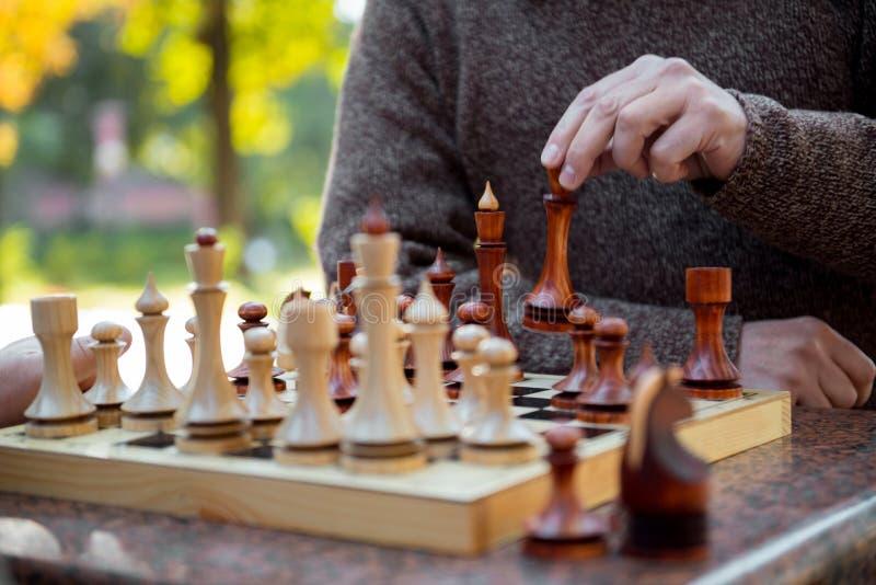 Ανώτερο αρσενικό κινούμενο statuette βραχιόνων στη σκακιέρα στοκ φωτογραφίες