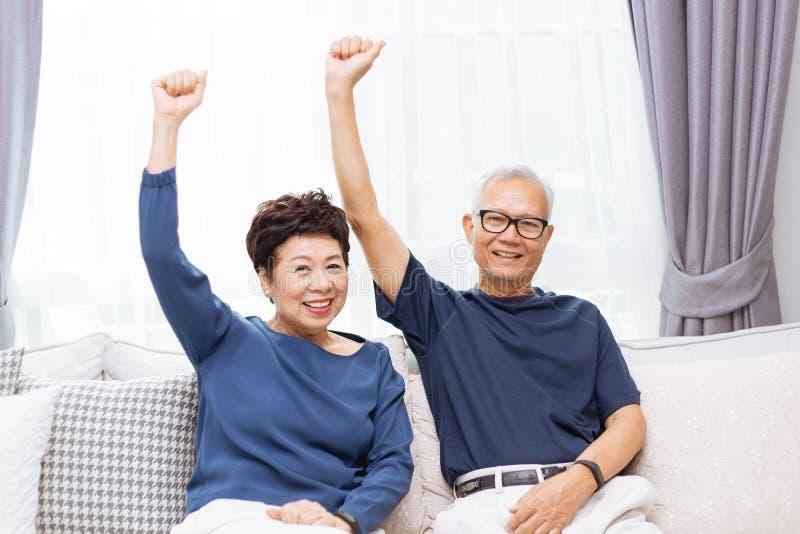 Ανώτερο ασιατικό ζεύγος που εξετάζει τη κάμερα και που αυξάνει τα χέρια επάνω καθμένος στον καναπέ στο σπίτι στοκ φωτογραφίες με δικαίωμα ελεύθερης χρήσης