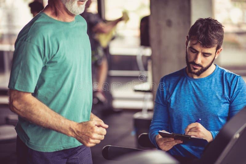Ανώτερο ατόμων treadmill, προσωπικός εκπαιδευτής που γράφει στο αρχείο στοκ φωτογραφίες με δικαίωμα ελεύθερης χρήσης