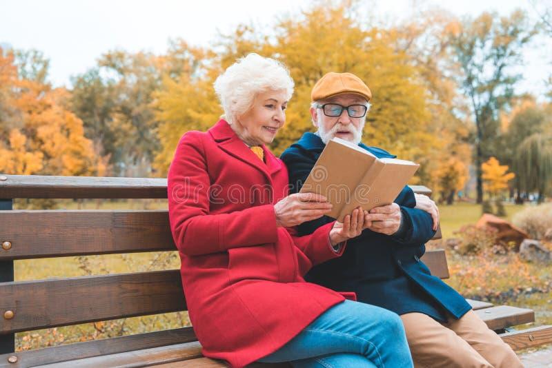 ανώτερο βιβλίο ανάγνωσης ζευγών καθμένος στον πάγκο στοκ εικόνες