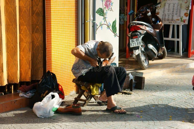 Ανώτερο βιετναμέζικο άτομο, παπούτσια επισκευής στοκ εικόνα