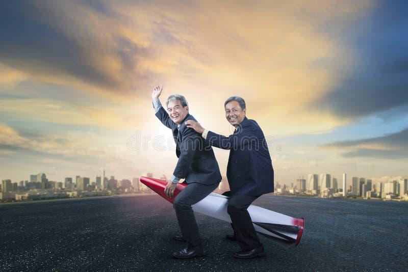Ανώτερο επιχειρησιακό δύο άτομο που οδηγά στο παιχνίδι πυραύλων παιδιών που στέκεται το ο στοκ εικόνα