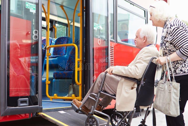 Ανώτερο λεωφορείο τροφής ζεύγους που χρησιμοποιεί την κεκλιμένη ράμπα πρόσβασης αναπηρικών καρεκλών στοκ εικόνες