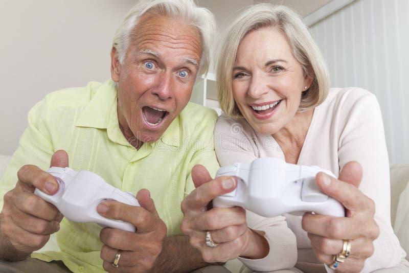 Ανώτερο ζεύγος ανδρών & γυναικών που παίζει το τηλεοπτικό παιχνίδι κονσολών στοκ φωτογραφία