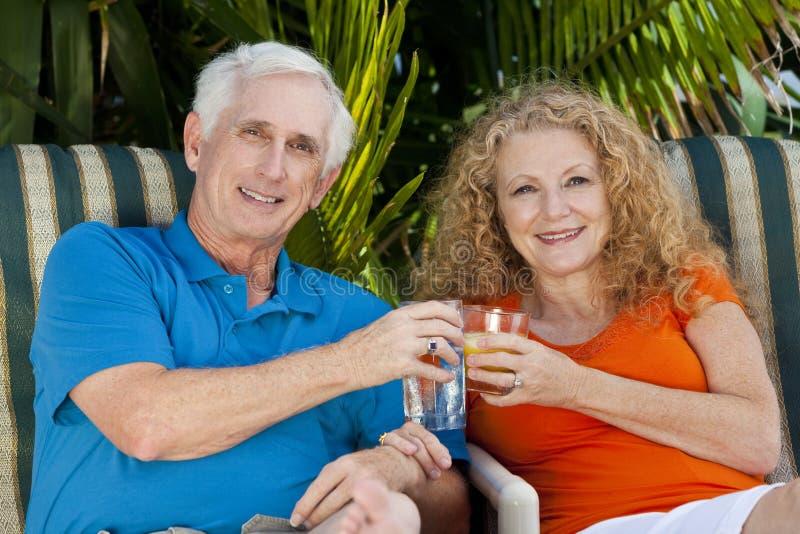Ανώτερο ζεύγος ανδρών και γυναικών που απολαμβάνει τα ποτά στοκ φωτογραφία