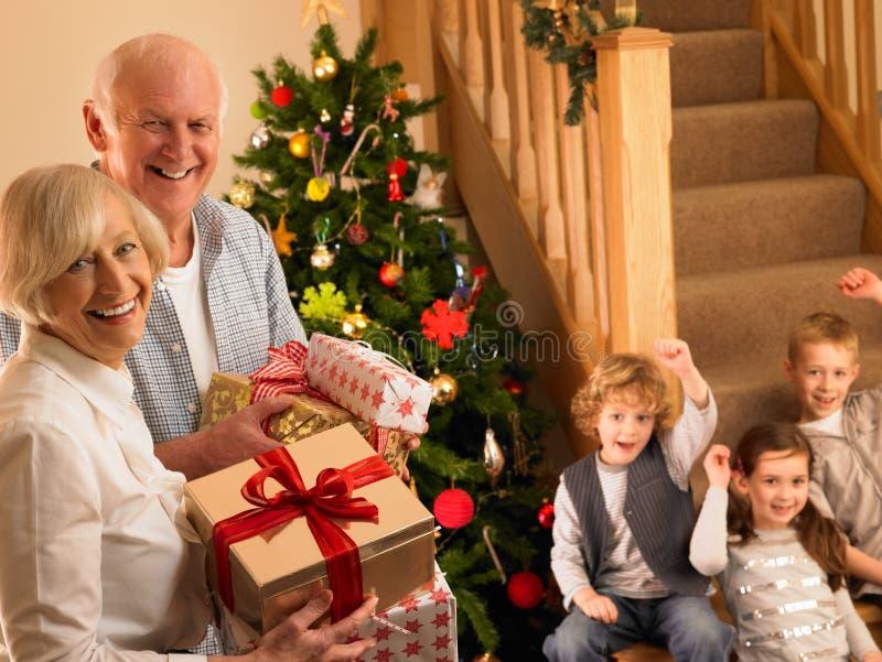 Ανώτερο ζεύγος με τα εγγόνια στα Χριστούγεννα στοκ φωτογραφία με δικαίωμα ελεύθερης χρήσης