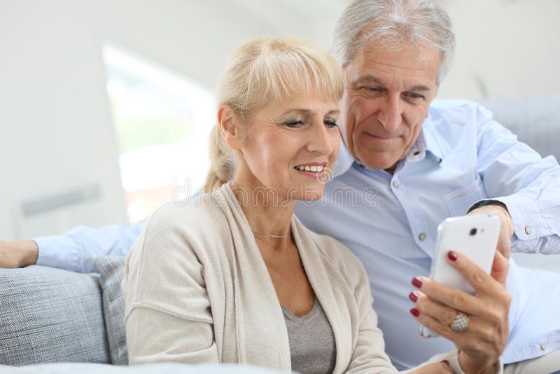 Ανώτερο ζεύγος με το smartphone στο σπίτι στοκ εικόνες με δικαίωμα ελεύθερης χρήσης