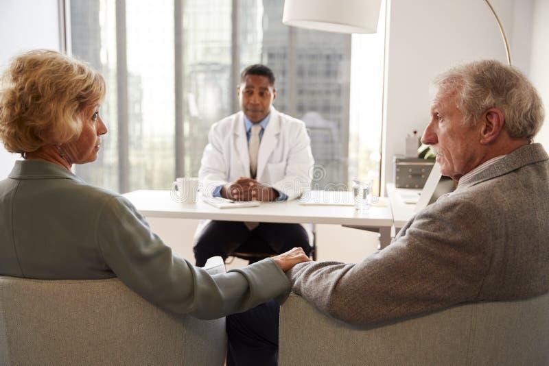 Ανώτερο ζεύγος που διοργανώνει τις διαβουλεύσεις με τον αρσενικό γιατρό στο γραφείο νοσοκομείων στοκ φωτογραφίες