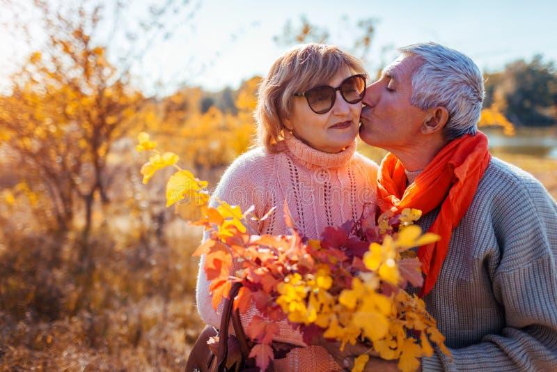 Ανώτερο ζεύγος που περπατά στο δασικό μέσης ηλικίας άνδρα φθινοπώρου που φιλά και που αγκαλιάζει τη γυναίκα στοκ εικόνες