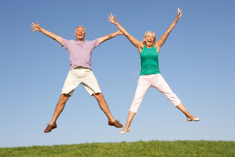 Download Ανώτερο ζεύγος που πηδά στον αέρα Στοκ Εικόνα - εικόνα από υγιής, lifestyle: 17059289