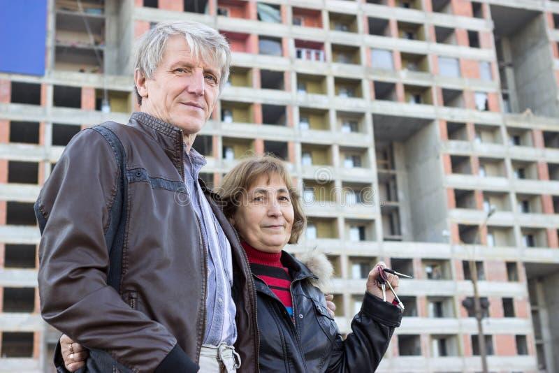 Ανώτερο ζεύγος που στέκεται με τα κλειδιά σπιτιών υπό εξέταση ενάντια στη πολυκατοικία στοκ φωτογραφία με δικαίωμα ελεύθερης χρήσης