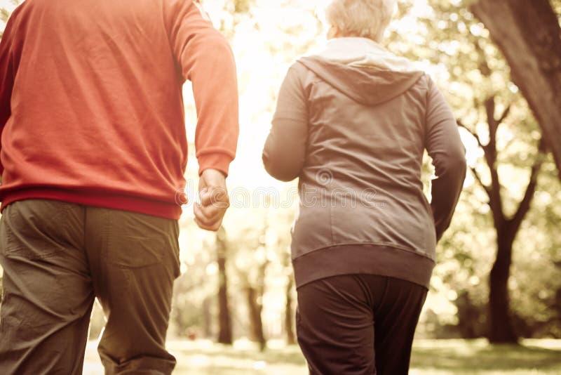 Ανώτερο ζεύγος που τρέχει στον αθλητισμό που ντύνει στο πάρκο στοκ εικόνα με δικαίωμα ελεύθερης χρήσης