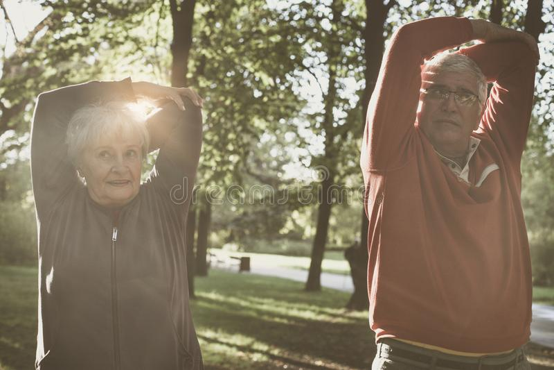 Ανώτερο ζεύγος που χαλαρώνει και άσκηση εργασίας μαζί στο πάρκο στοκ εικόνα