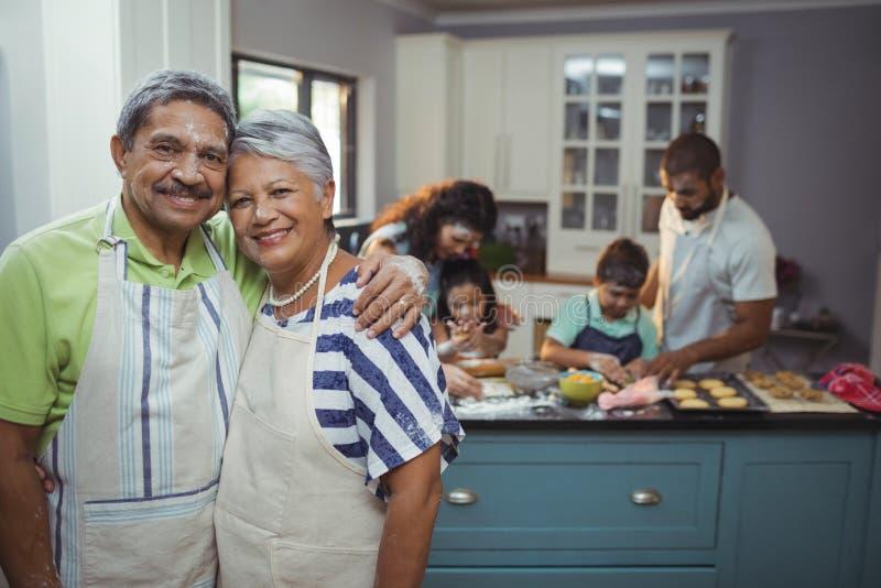Ανώτερο ζεύγος που χαμογελά στη κάμερα ενώ οικογενειακά μέλη που προετοιμάζουν το επιδόρπιο στο υπόβαθρο στοκ φωτογραφίες