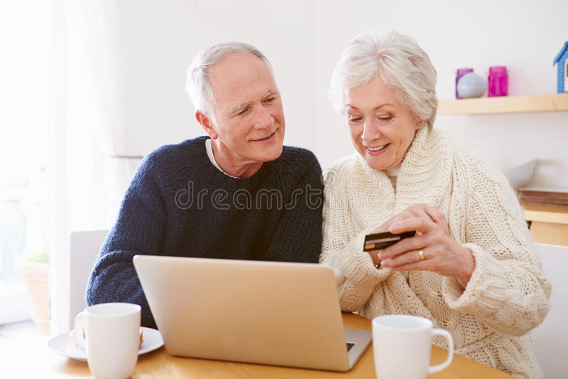 Ανώτερο ζεύγος που χρησιμοποιεί το lap-top για να ψωνίσει on-line στοκ φωτογραφία
