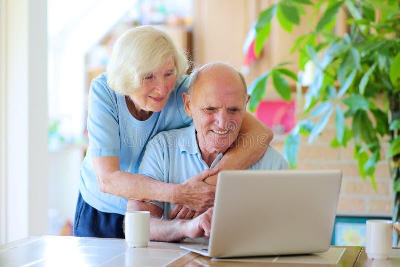 Ανώτερο ζεύγος που χρησιμοποιεί το lap-top στο σπίτι στοκ εικόνες