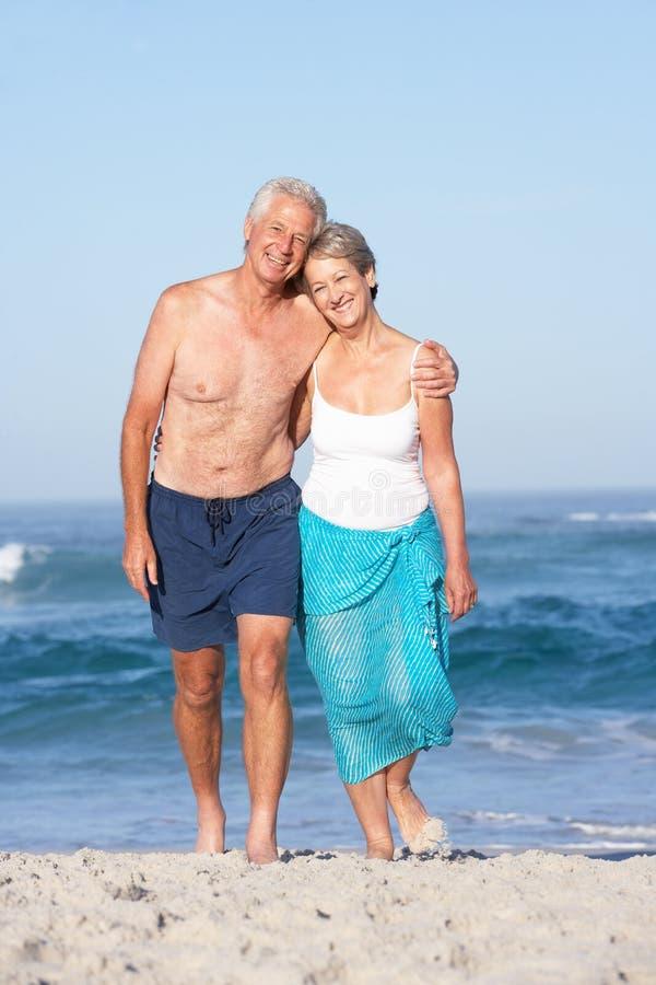 Ανώτερο ζεύγος στις διακοπές που περπατά κατά μήκος της αμμώδους παραλίας στοκ φωτογραφίες