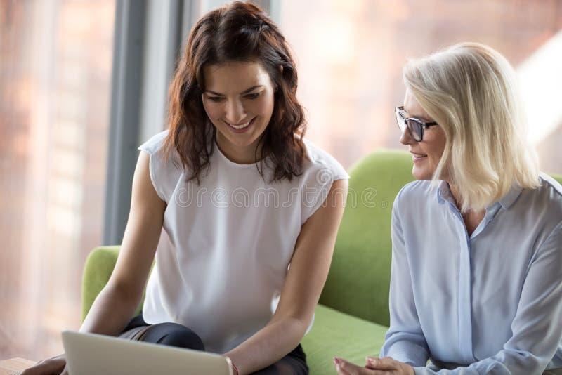 Ανώτερο και νέο κάθισμα γυναικών συναδέλφων που εξετάζει το lap-top scre στοκ εικόνα με δικαίωμα ελεύθερης χρήσης