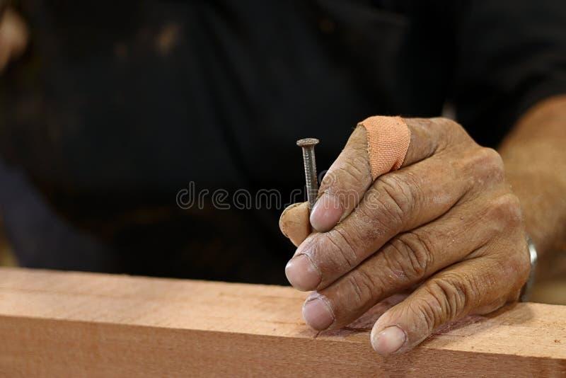 Ανώτερο καρφί εκμετάλλευσης ξυλουργών χεριών στο ξύλινο κομμάτι με το διάστημα αντιγράφων στοκ φωτογραφία με δικαίωμα ελεύθερης χρήσης