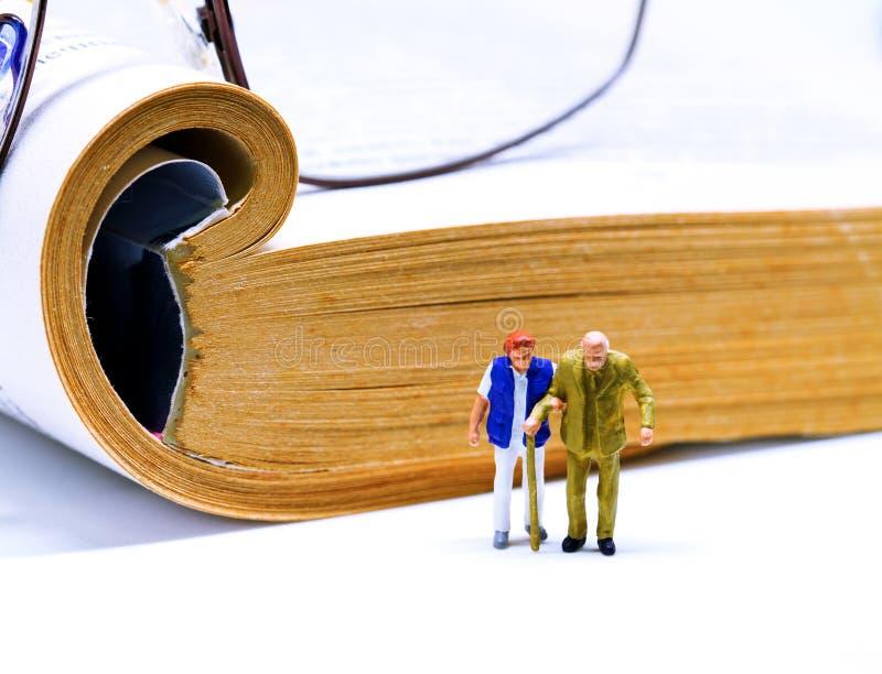 Ανώτερο μικροσκοπικό ειδώλιο ζευγών με το βιβλίο και γυαλιά στο υπόβαθρο στοκ φωτογραφίες με δικαίωμα ελεύθερης χρήσης