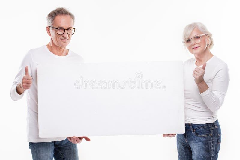 Ανώτερο όμορφο ζεύγος με τον κενό λευκό πίνακα στοκ φωτογραφίες