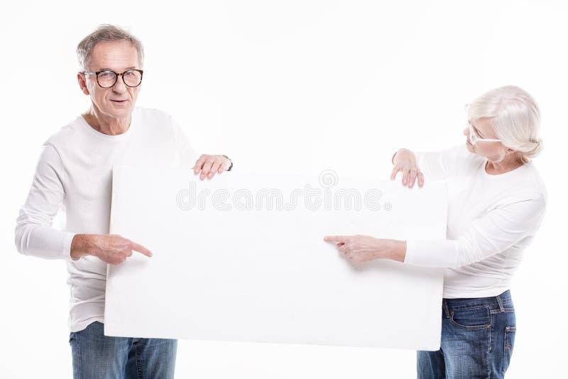 Ανώτερο όμορφο ζεύγος με τον κενό λευκό πίνακα στοκ εικόνα με δικαίωμα ελεύθερης χρήσης