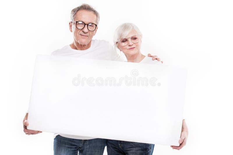 Ανώτερο όμορφο ζεύγος με τον κενό λευκό πίνακα στοκ εικόνα
