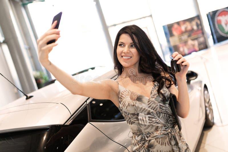 Αξιοθαύμαστος brunet κάνει ένα selfie και κοντά στο νέο αυτοκίνητό της στην αίθουσα εκθέσεως αντιπροσώπων στοκ εικόνες