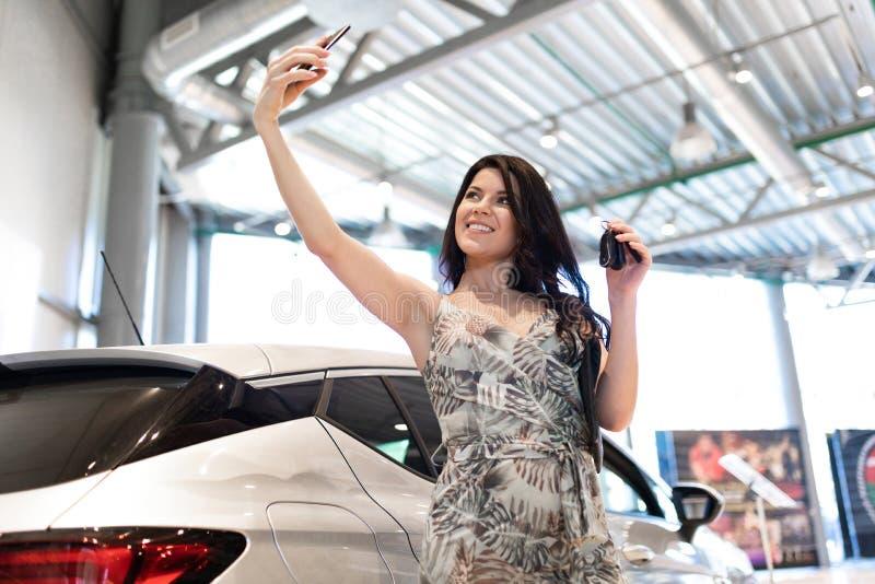 Αξιοθαύμαστος brunet κάνει ένα selfie και κοντά στο νέο αυτοκίνητό της στην αίθουσα εκθέσεως αντιπροσώπων στοκ φωτογραφία