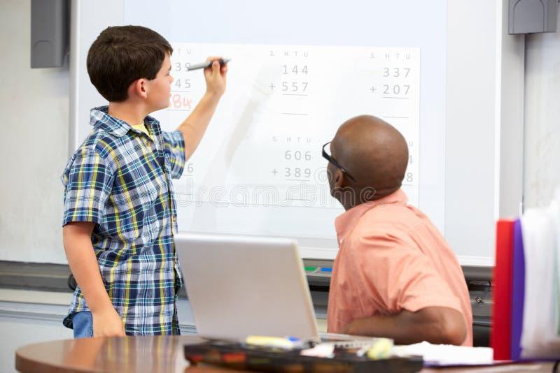 Απάντηση γραψίματος ανδρών σπουδαστών σε Whiteboard στοκ φωτογραφία με δικαίωμα ελεύθερης χρήσης