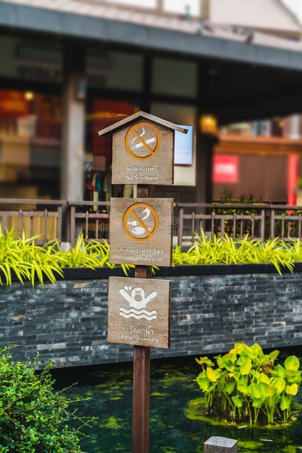 Απαγορεύεται το κάπνισμα, μην ταΐζεις ψάρια και προσεκτικός πνιγμός Σήμανση στο πάρκο στοκ εικόνα