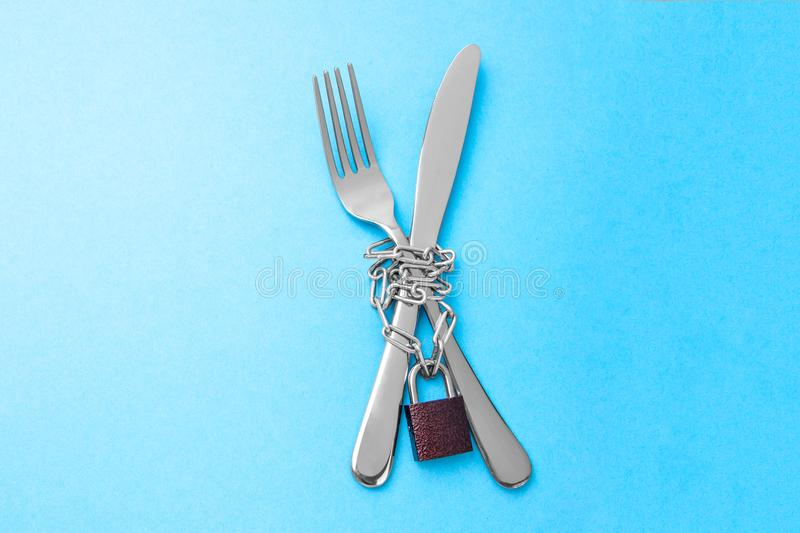 Απαγόρευση στα τρόφιμα ως διατροφή για την απώλεια βάρους Το δίκρανο και το μαχαίρι είναι τυλιγμένα σε μια αλυσίδα και κλειδωμένα στοκ φωτογραφία με δικαίωμα ελεύθερης χρήσης