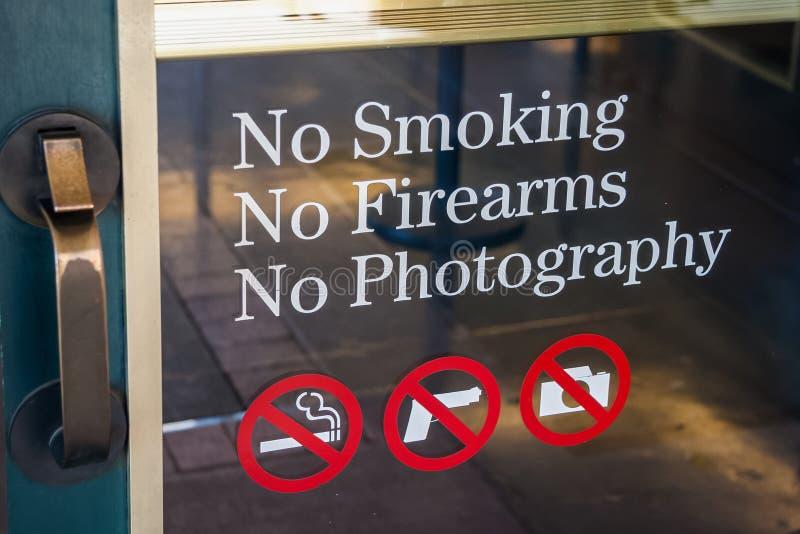 Απαγόρευση του καπνίσματος, κανένα πυροβόλο, κανένα σημάδι φωτογραφίας στην είσοδο πορτών στοκ φωτογραφία με δικαίωμα ελεύθερης χρήσης