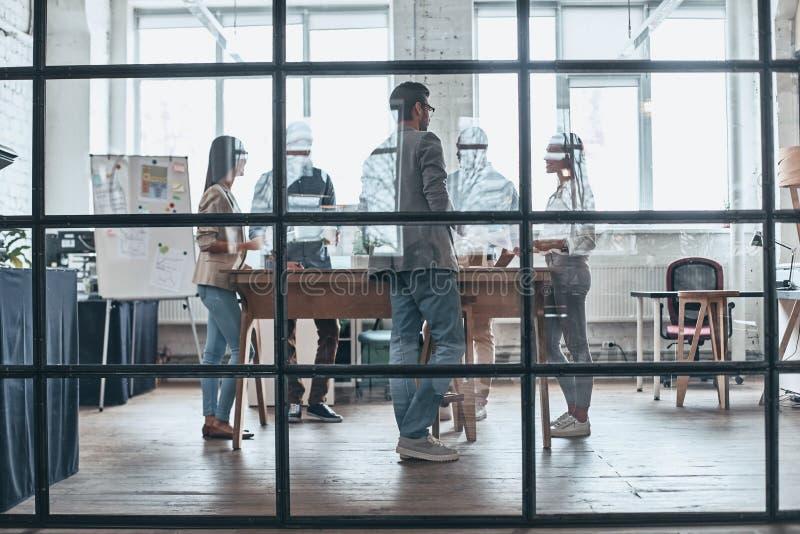 απασχολημένη εργασία ημέρας Πλήρες μήκος των σύγχρονων νέων που εργάζονται και στοκ φωτογραφία