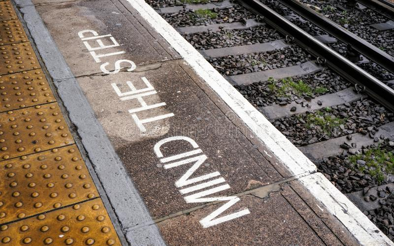 ΑΠΑΣΧΟΛΗΣΤΕ το STEP που γράφεται στην πλατφόρμα τραίνων κοντά στις ράγες στον ελαφρύ σιδηροδρομικό σταθμό του Λονδίνου DLR Dockla στοκ φωτογραφίες