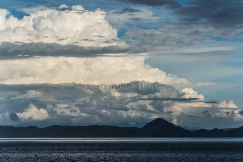 Απειλητικά καλά σύννεφα πέρα από τους σκούρο μπλε λόφους κοντά στην ήρεμη ωκεάνια Σιγκαπούρη στοκ φωτογραφίες με δικαίωμα ελεύθερης χρήσης