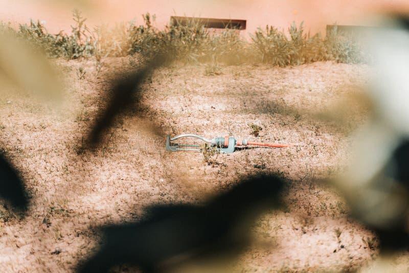 Απελπισμένος για να υγράνει το ξηρό χώμα με έναν ψεκαστήρα στοκ φωτογραφία με δικαίωμα ελεύθερης χρήσης