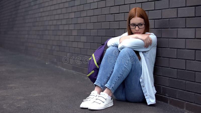 Απελπισμένος φοιτητής που κάθεται στην πίσω αυλή του σχολείου, ανασφάλεια στην εφηβεία στοκ φωτογραφίες