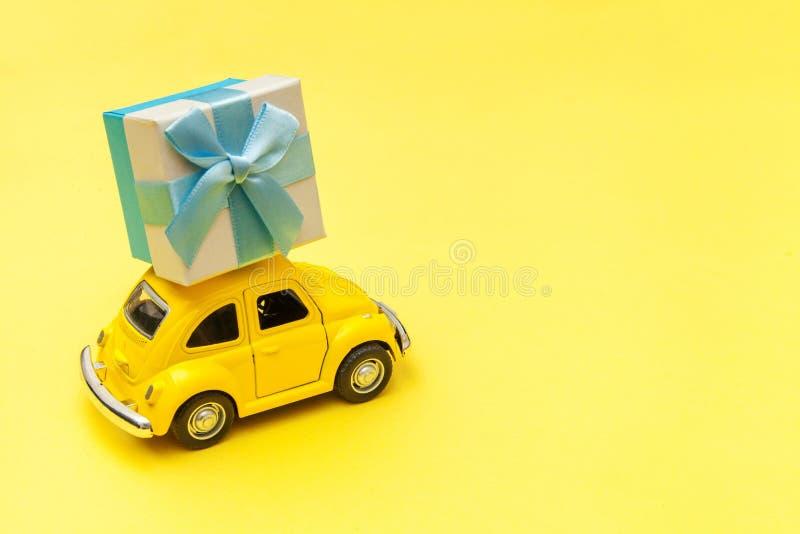 Απλά σχεδιάστε ένα κίτρινο παραδοσιακό ρετρό αυτοκίνητο που παραδίδει ένα κουτί δώρο στην οροφή απομονωμένο σε μοδάτο κίτρινο φόν στοκ φωτογραφία με δικαίωμα ελεύθερης χρήσης