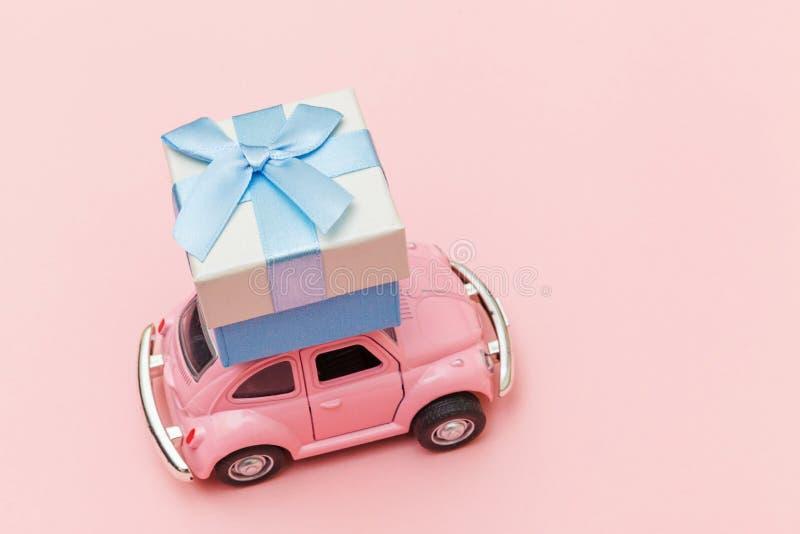 Απλά σχεδιάστε ροζ παραδοσιακό ρετρό αυτοκίνητο που παραδίδει ένα κουτί δώρο στην οροφή απομονωμένο σε μοδάτο παστέλ ροζ φόντο Χρ στοκ φωτογραφία με δικαίωμα ελεύθερης χρήσης