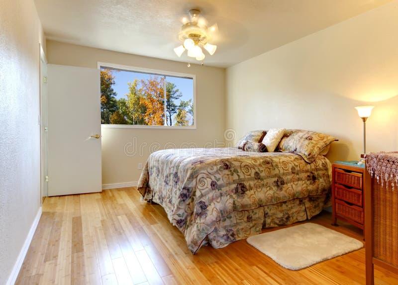 Απλή κρεβατοκάμαρα με το πάτωμα ξυλείας πλατύφυλλων και την όψη παραθύρων πτώσης. στοκ εικόνα