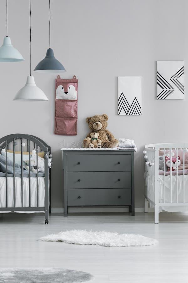 Απλό, γκρι και λευκό εσωτερικό δωμάτιο για δύο μικρά παιδιά με ένα στήθος από συρτάρια μεταξύ δύο ξύλινων κρεβατιών Πραγματική φω στοκ εικόνα